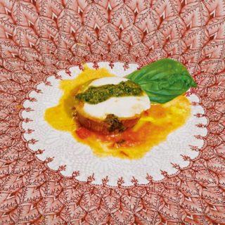 Ein mit Mozzarella überzogenes Auberginen-Medaillon mit Pesto auf einem gemusterten Teller.