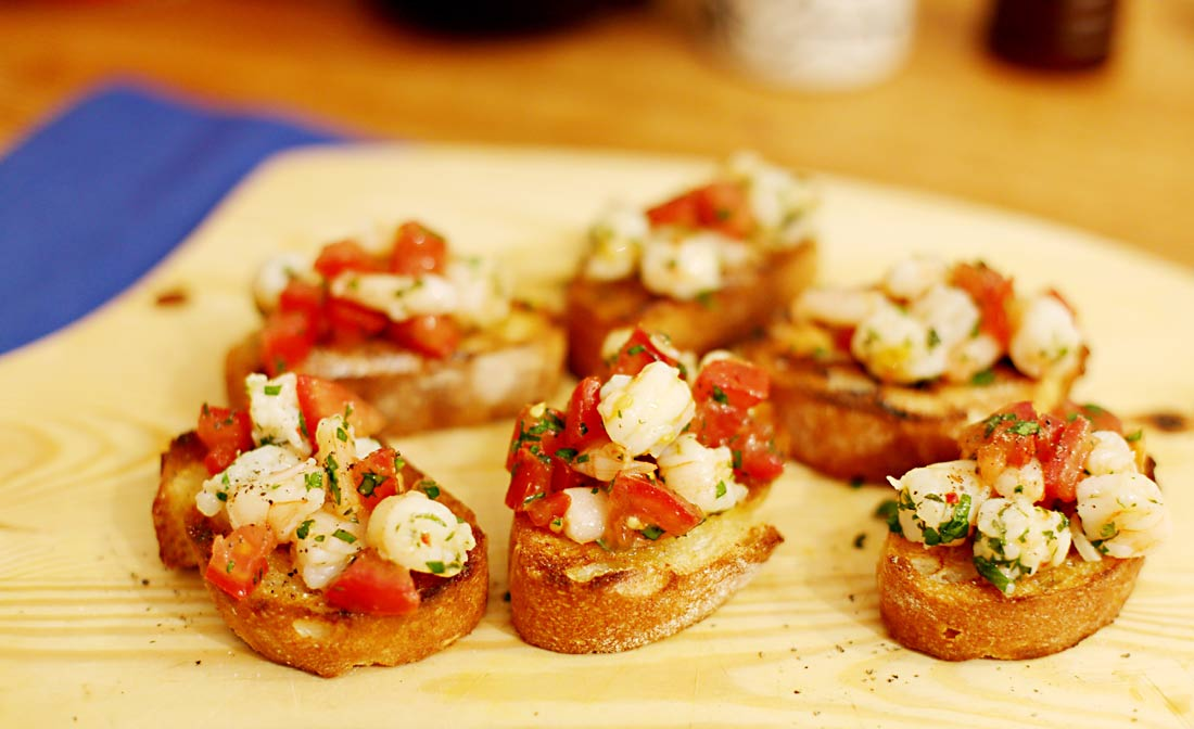 Sechs Bruschettascheiben belegt mit Garnelen und Tomaten