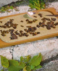 Auf einem Holzbrett wird der umbrische Wilderbsenbrei Farrecchiata serviert.