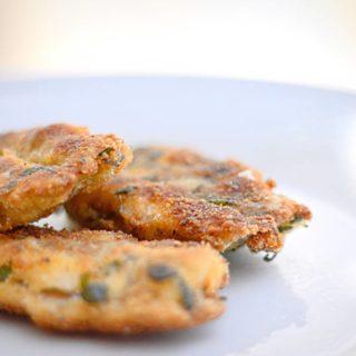 Drei panierte, mit Auberginen gefüllte Sardellen auf einem weißen Teller.