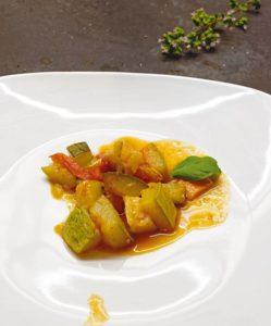 Auf einem weißen Teller ist geschmortes Gemüse in einer Tomatesauce angerichtet.