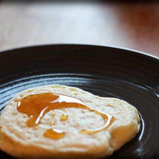 Ein marokkanischer Pfannkuchen mit Honigsirup auf einem braunen Teller.