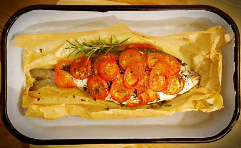 In einer Backofenform liegt eine Dorade, die mit Tomatenscheiben und Kräutern belegt ist.