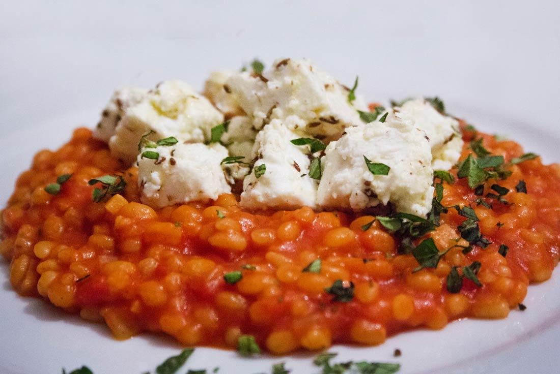 Graupenrisotto in Tomate mit mariniertem Feta, bestreut mit Oregano.