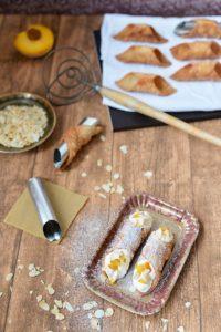 Zwei mit Ricotta und Pfirsichstückchen gefüllte Canolli. Im Hintergrund weitere Canolli-Röllchen, die noch gefüllt werden müssen.