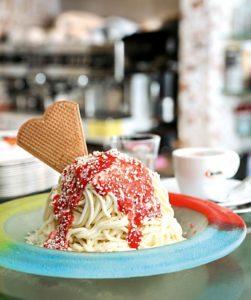 Ein bunter Teller mit einer Portion Spaghetti-Eis mit Erdbeersauce und einer Eiswaffel.