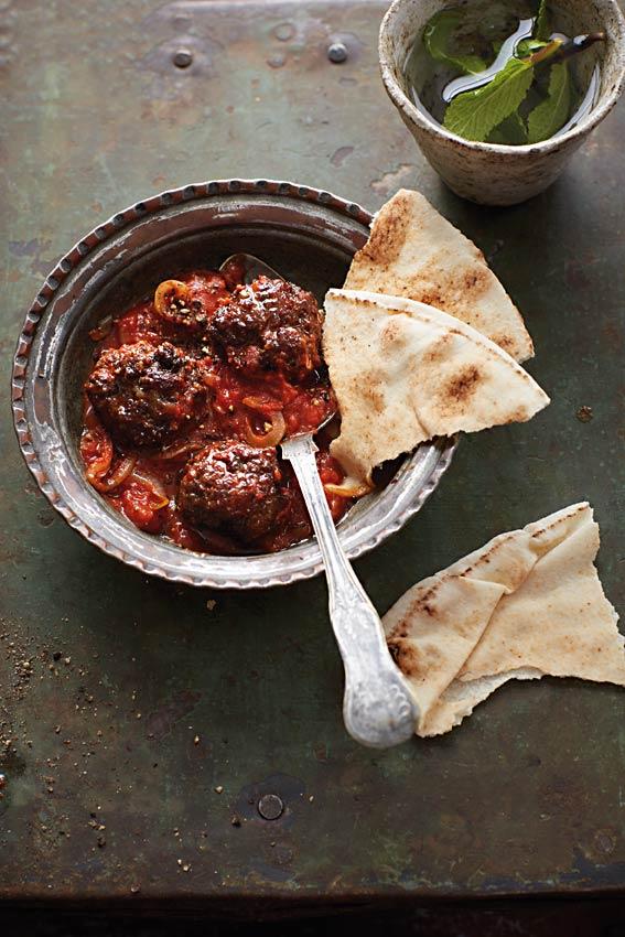 Eine Schale mit frittierten Hackbällchen in Tomatensauce, daneben etwas arabisches Fladenbrot.