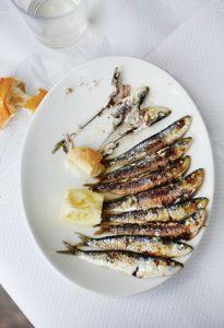 Ein weißer Teller mit gegrillten Sardinen a la plancha