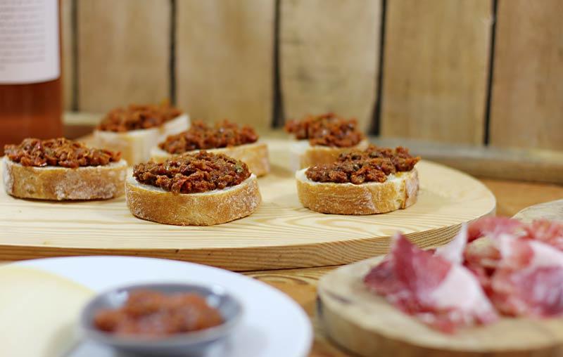 Bruschetta-Scheiben mit einem Aufstrich aus getrockneten Tomaten auf einem Holzbrett