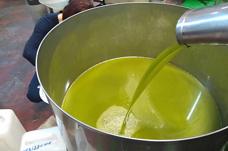 Ein großes Gefäß, in das frisches Olivenöl fließt.