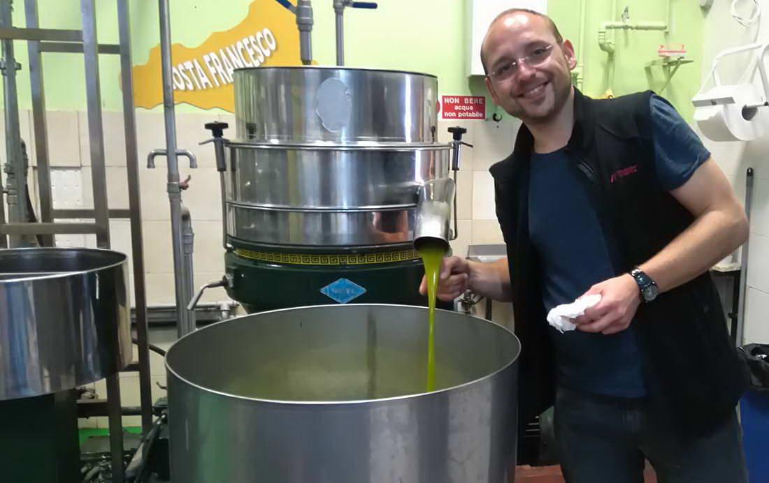 Olivenölverkoster Arkadius Michalczyk neben einer Olivenpresse