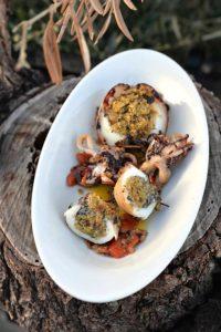 Ein ovaler Teller mit gefüllten Tintenfischen, er steht auf einem Baumstumpf