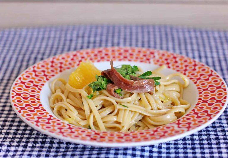 Ein Teller mit gekochten Linguine, garniert mit Orange, Sardellen und Petersilie