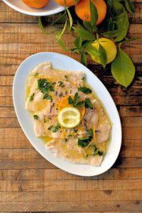 Ein ovaler Teller mit Schwertfisch-Carpaccio, das in einer Mandarinensauce mariniert wurde.