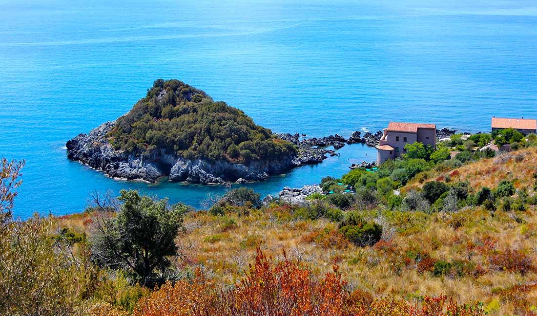 Eine Mini-Insel, direkt an der Küste der Basilikata, vor der ein paar Menschen baden.