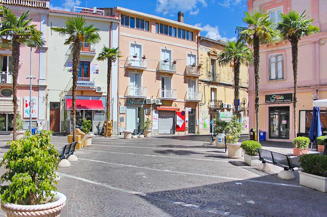 Ein Platz mit Palmen und Bänken in Amantea