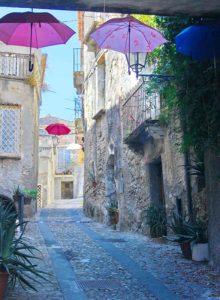 Eine Gasse in der Altstadt von Amantea, in der aufgespannte Regenschirme hängen