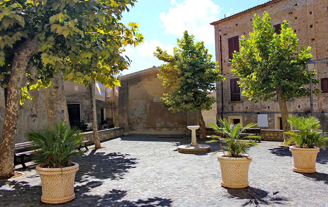 Eine kleine Piazza mit Pflanzen in Blumenkübeln in Fiumefreddo Bruzio.