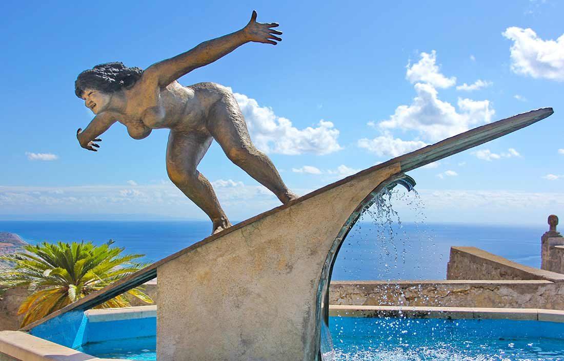 Ein Brunnen mit der Statue einer nackten Frau auf einem Surfbrett