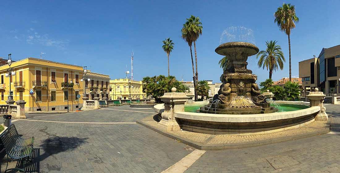 Die Piazza Amendola in Palmi mit einem Brunnen in der Mitte und einer Parkbank.