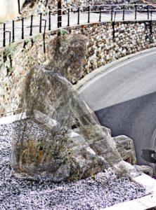 Eine Skulptur aus Draht eines sitzenden Menschen.
