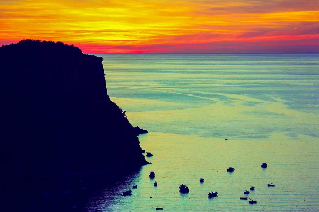 Die Isola di Dino, hinter der die Sonne untergeht. Auf dem Meer ankern Schiffe.