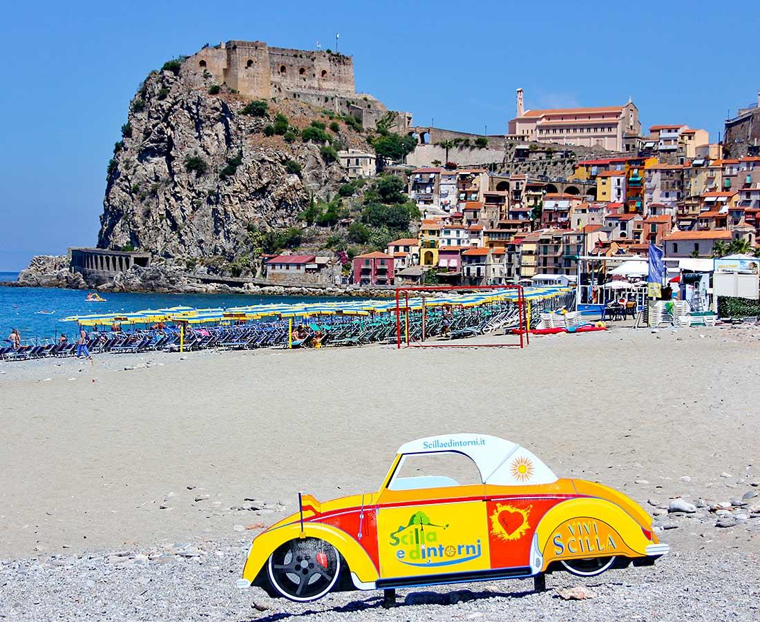 Die Häuser des Stadtteils Marina Grande in Scilla, davor der Strand mit einem Willkommensschild