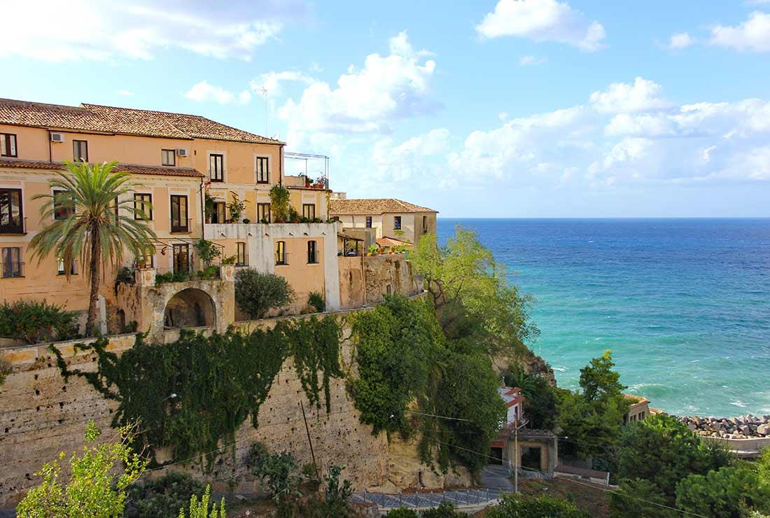 Ein Palazzo an der steilen Küste Tropeas, im Hintergrund das Meer
