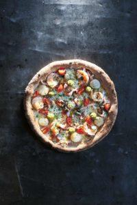 Eine runde Pizza, belegt mit Meeresfrüchten wie Scampi und Jakobsmuscheln, Kirschtomaten und Avocadocreme.