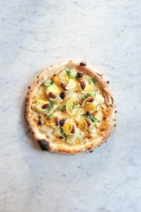 Eine runde Pizza belegt mit Birnenspalten, Ziegenkäse, Pekanüssen und feinen Blutorangenscheiben.