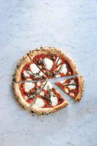 Eine runde Pizza, die in acht Stücke geschnitten wurde. Sie ist belegt mit Sardellenfilets, Tomatensauce, Mozzarella, Oliven und Kapern.