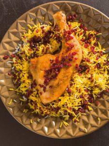 Ein Teller mit gelb gefärbten Safranreis mit Berberitzen. Darauf liegt ein krosser Hähnchenschenkel.