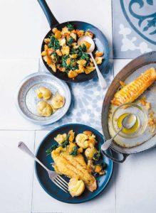 Auf einem Kachelboden stehen zwei eiserne Pfannen und zwei Teller. In einer Pfanne und auf einem Teller liegt gegrillter Klippfisch, in der anderen Pfanne sind Migas und auf dem zweiten Teller Kartoffeln.