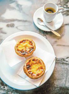 Auf einem weißen Teller liegen zwei kleine gebackene Cremetörtchen. Daneben steht eine Tasse mit Kaffee.