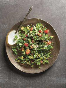 Auf einem Kupferteller ist ein Salat aus Kräutern angerichtet.