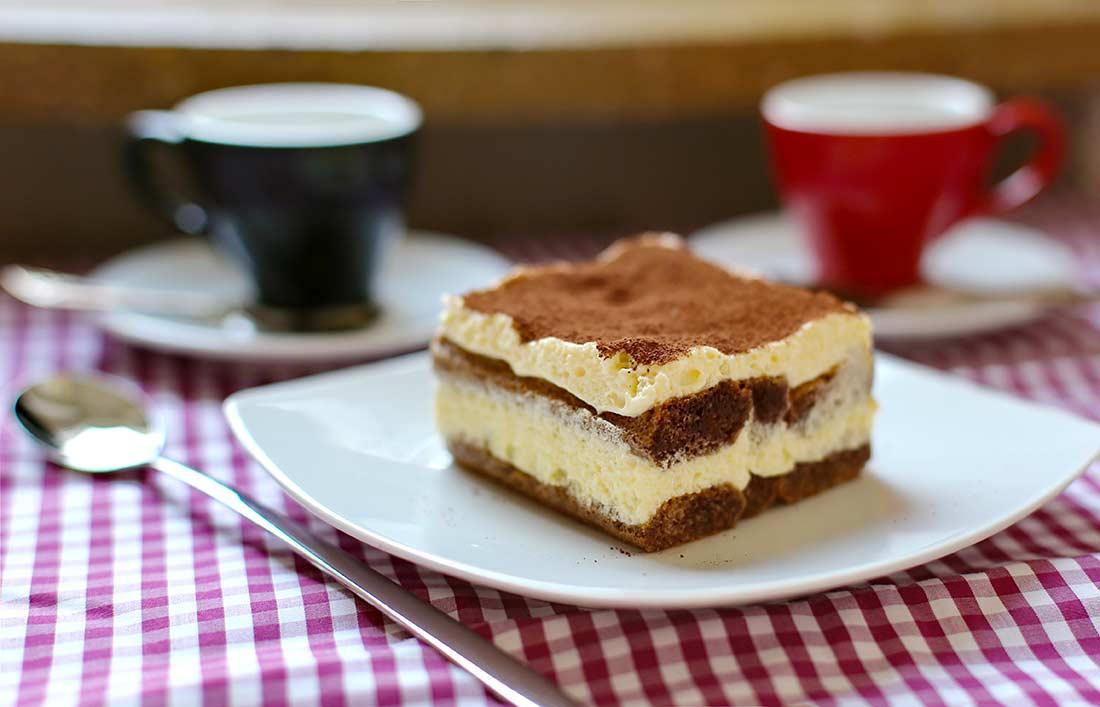 Ein Stück Tiramisu auf einem viereckigen Teller. Im Hintergrund zwei Espressotassen.
