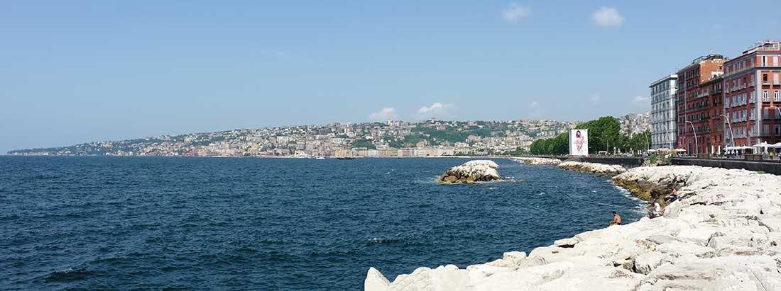 Panoramaaufnahme des Golf von Neapel mit den Stadtteilen Chiaia und Posillipo. Im Vordergrund das Meer.
