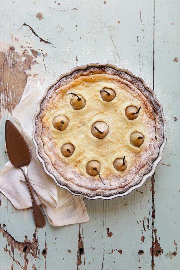 Auf einem Holzbrett steht eine Tarte mit Birnen, daneben eine Kuchengabel und ein Geschirrtuch.