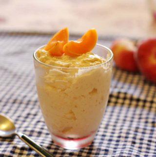 Ein Glas mit Aprikosencreme. Im Hintergrund liegen Pfirsiche.