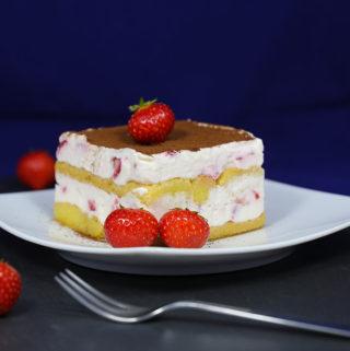 Auf Stück Erdbeer-Tiramisu auf einem Teller, garniert mit frischen Erdbeeren.