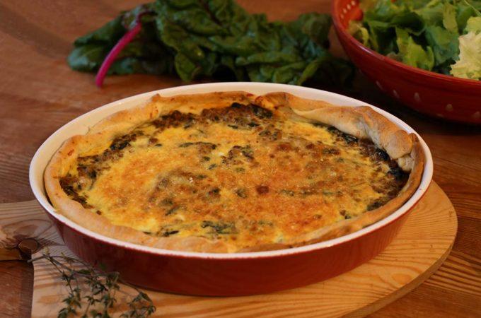 Eine Quiche mit Mangold und Hackfleisch in einer Ofenform auf einem Tablett.