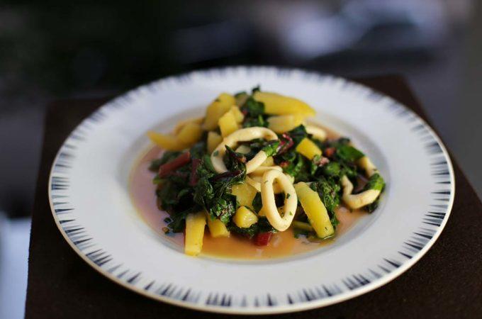 Ein Teller mit Tintenfischringen an Kartoffeln und Mangold