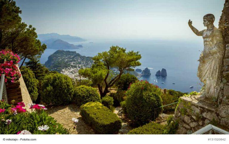 Blick über Capri und das Meer vom Monte Solaro aus. Im Vordergrund ein Garten und eine Statue. Ein Foto von mikolajn / Fotolia.