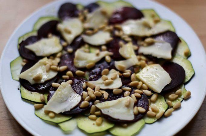 Ein Teller mit einem Carpaccio aus Rote Bete, Zucchini und Scamorza, bestreut mit Pinienkernen.