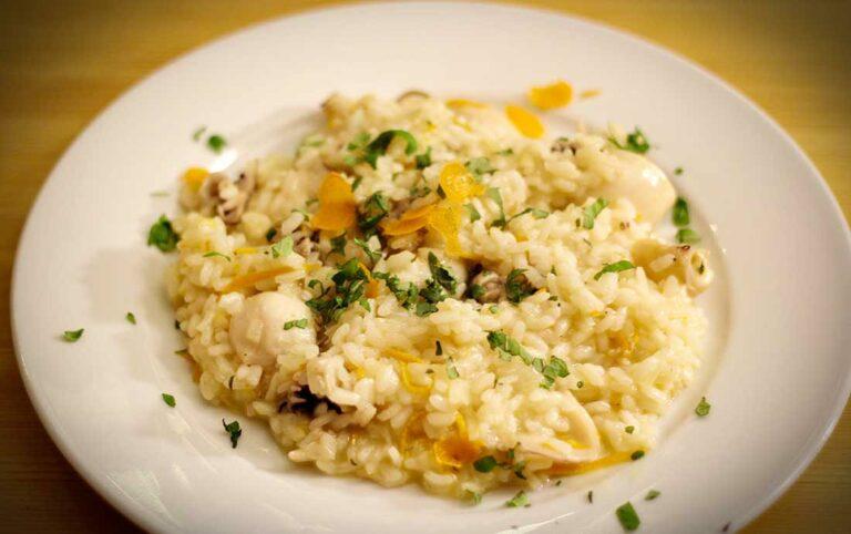 Ein Teller mit Orangenrisotto mit kleinen Calamari.