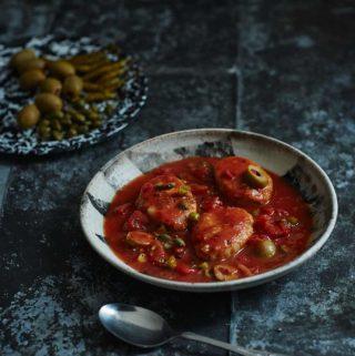Ein Teller mit Gefilte Fisch in einer mexikanischen Tomaten-Oliven-Kapern-Sauce.