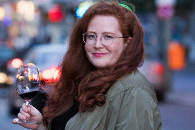 Autorin Liv Fleischhacker mit einem Glas Wein in der Hand