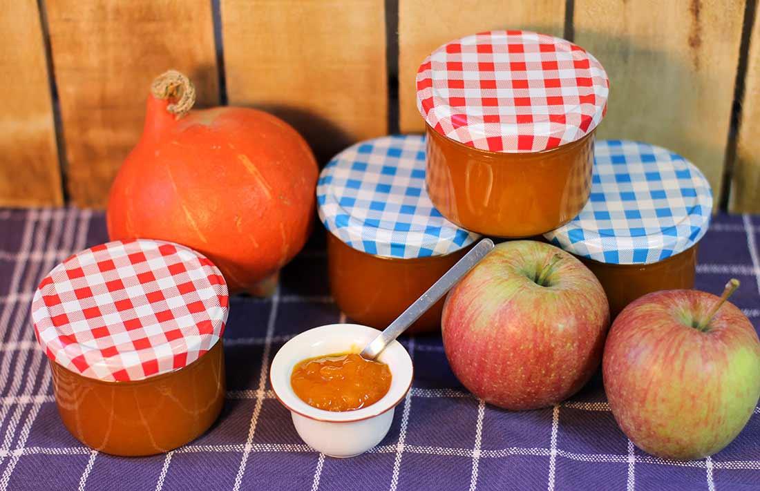 Marmeladengläser, ein Kürbis, zwei Äpfel und ein Töpfchen mit Apfel-Kürbis-Marmelade