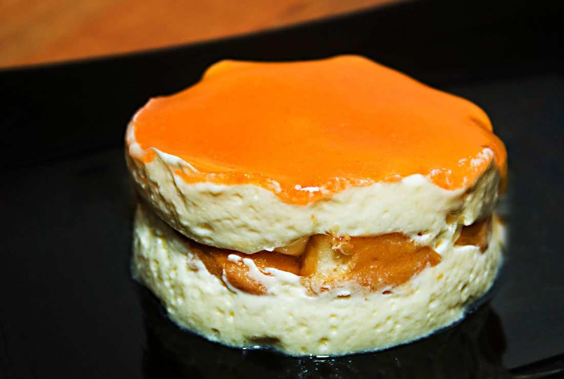 Ein rundes Stück Tiramisu mit fruchtigem Kakipüree glasiert.