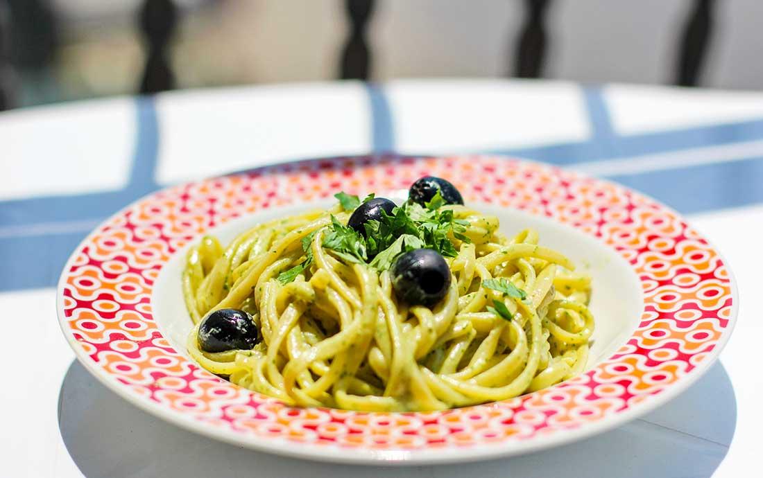 Ein Teller mit Nudeln in Thunfischsauce und Oliven.